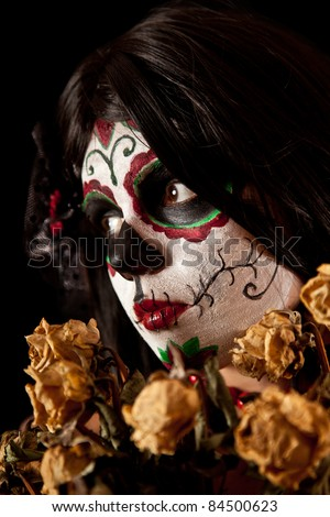 Portrait of Sugar skull girl with dead roses, isolated on black background - stock photo