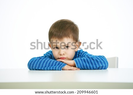 Portrait of sullen little boy sitting at table, looking at camera, serious. - stock photo