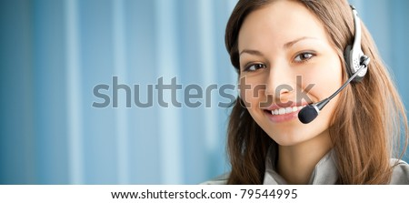 Portrait of support phone operator in headset at workplace. To provide maximum quality, I have made this image by combination of two photos. You can use left part for slogan, big text or banner. - stock photo