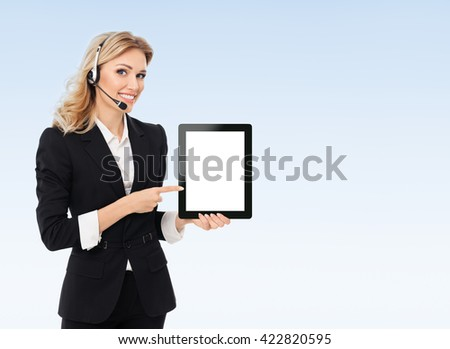 Portrait of support phone operator in headset showing blank no-name tablet pc monitor, with copyspace area for text or slogan, on blue background - stock photo