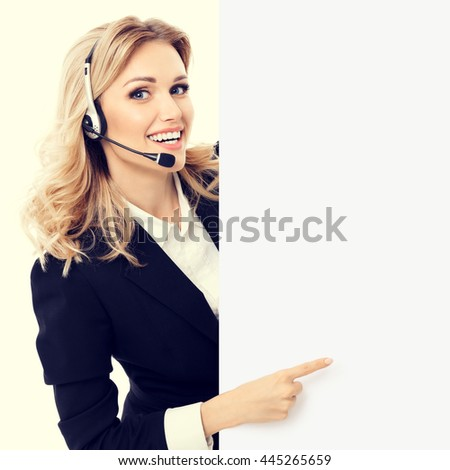 Portrait of support phone operator in headset showing blank signboard with copyspace area for text or slogan