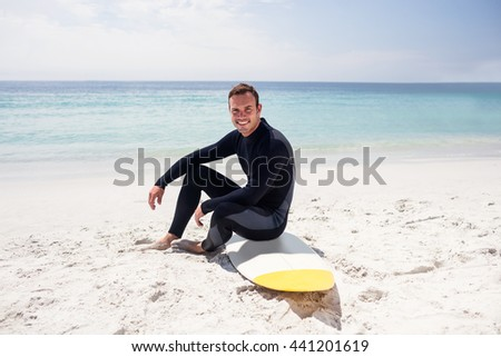 Portrait of surfer in wetsuit sitting with surfboard on the beach on a sunny day - stock photo