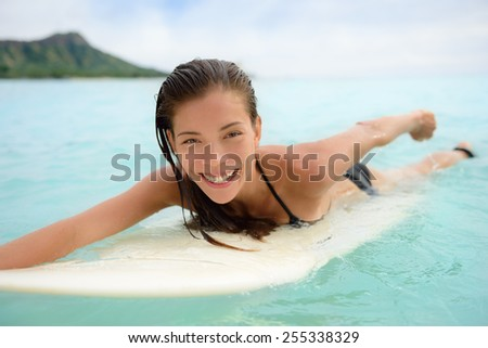 Portrait of surfer woman surfing having fun on Waikiki Beach, Oahu, Hawaii. Female bikini girl laughing on surfboard smiling happy living healthy lifestyle on Hawaiian beach. Asian Caucasian model. - stock photo