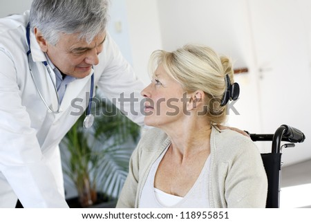 Portrait of surgeon talking to patient in wheelchair - stock photo