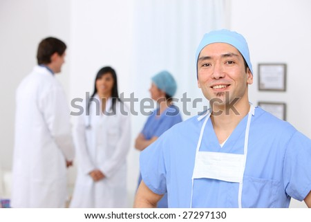 Portrait of surgeon with other medical personnel in background