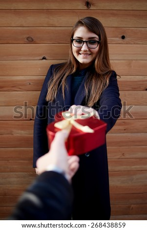 Portrait of surprised cheerful girl taking Saint Valentine's present from her boyfriend looking to the camera - stock photo
