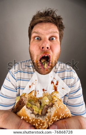 Portrait of surprised dirty man chewing hamburger - stock photo