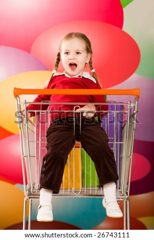 Portrait of surprised girl sitting in handcart and shouting in the mall - stock photo