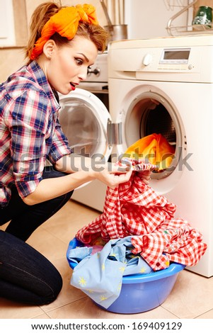 Portrait of surprised housewife spotting a stain on the laundry - stock photo
