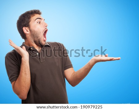 portrait of surprised man holding something in his hand - stock photo