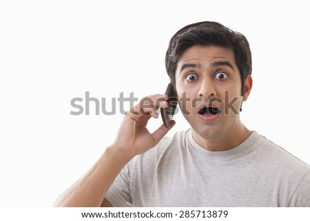 Portrait of surprised man using cell phone over white background