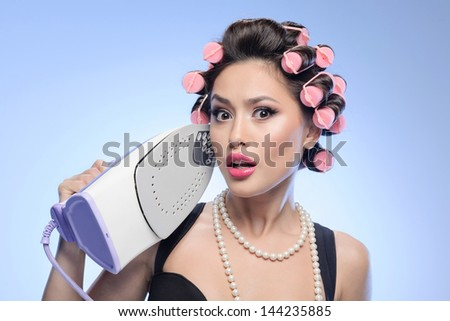 Portrait of surprised sexy housewife holding an iron. Surprised sexy housewife holding an iron in her hand