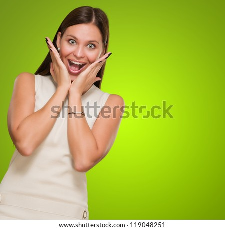 Portrait Of Surprised Woman against a green background - stock photo