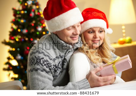 Portrait of surprised woman looking at giftbox in her husband hands while being embraced by him - stock photo