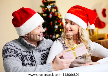 Portrait of surprised woman looking at her husband with giftbox on xmas day - stock photo