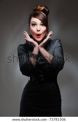 portrait of surprised woman over dark background - stock photo