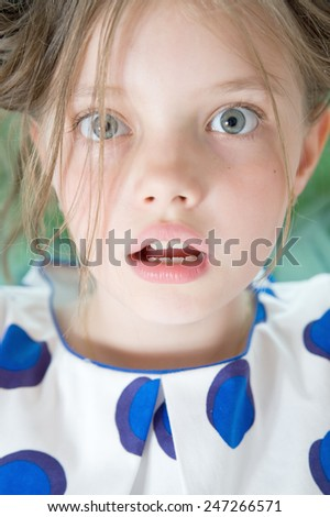 Portrait of surprised 8 year old girl close up (studio photography)