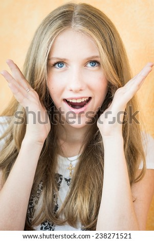 Portrait of surprised young beautiful girl with mouth open and hands near face. Positive facial expression.  - stock photo