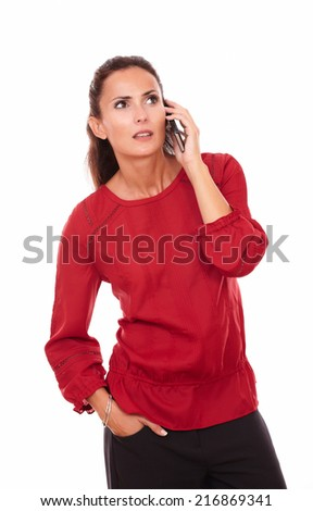 Portrait of surprised young lady on red shirt talking on her cellphone while standing on isolated white background - copyspace - stock photo