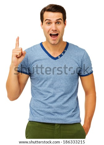 Portrait of surprised young man pointing upwards while standing against white background. Vertical shot. - stock photo