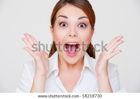portrait of surprised young woman over grey background - stock photo