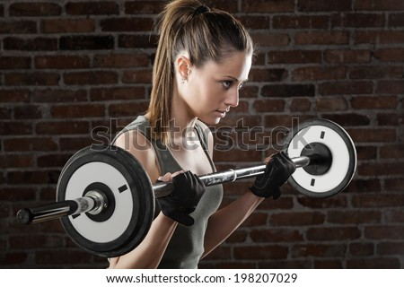 Portrait of Sweat beautiful girl lifting dumbbells on dark background  - stock photo