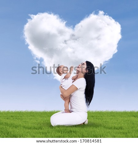Portrait of sweet baby and his mother with heart shaped cloud - stock photo