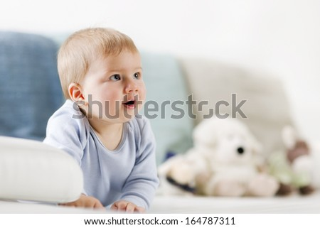 Portrait of sweet baby boy with blue eyes lying on his tummy and looking up with mouth open, blurred toys in background. - stock photo
