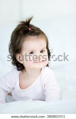Portrait of sweet baby little girl lying on the front in the bed.Baby looking at camera.Shallow doff
