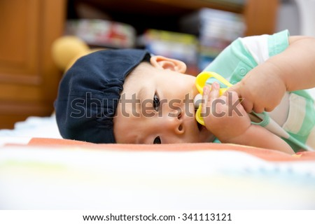 Portrait of sweet baby wearing blue hat. Baby chewing on teething plastic toy - stock photo