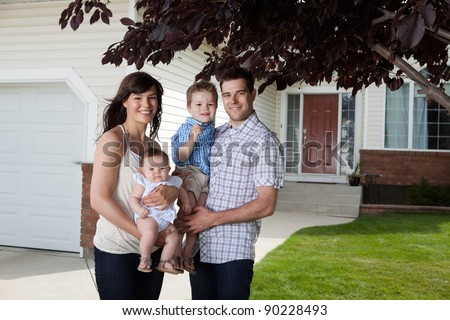 Portrait of sweet family standing in front of their house - stock photo