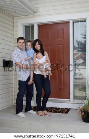 Portrait Of Sweet Family Standing In Front Of Their House.