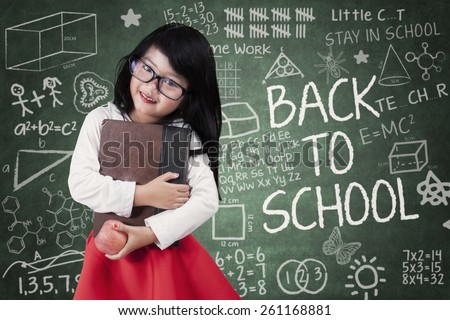 Portrait of sweet girl back to school and smiling at the camera while standing in the class - stock photo
