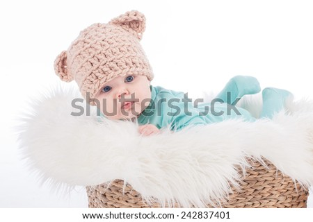 Portrait of sweet three months old baby girl in knitted brown bear hat with ears on a fluffy blanket in basket - stock photo