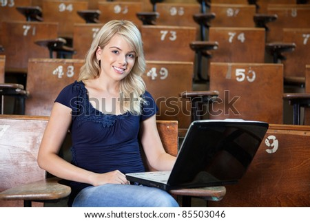 Portrait of sweet young college girl using laptop in university lecture hall - stock photo