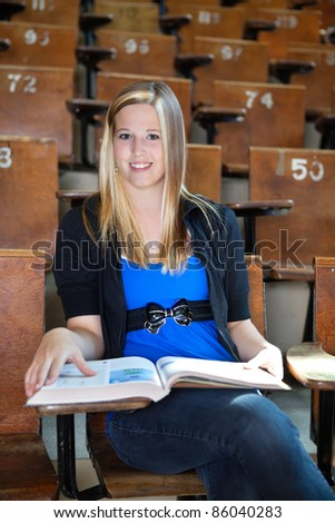 Portrait of sweet young girl attending lecture at university hall - stock photo