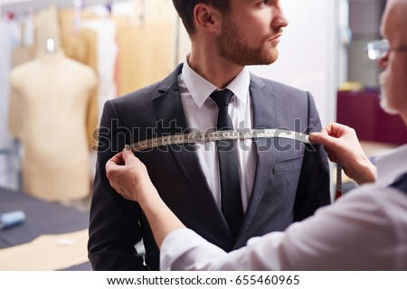 Portrait of tailor taking measurements of customer during model fitting