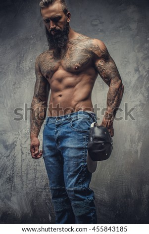 Portrait of tattooed bearded male in denim jeans and naked torso over grey background.