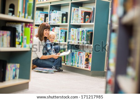 Portrait of teacher and boy reading book by bookshelf in library - stock photo