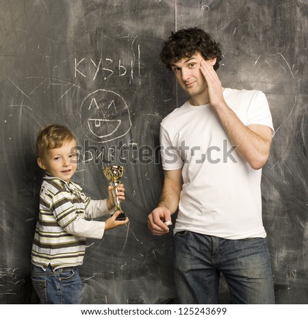portrait of teacher and little pupil, father and son near blackboard - stock photo