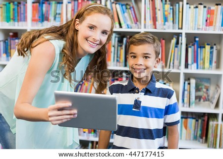 Portrait of teacher and school boy using digital tablet in library at school - stock photo