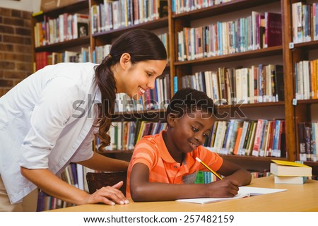 Portrait of teacher assisting little boy with homework in the library - stock photo