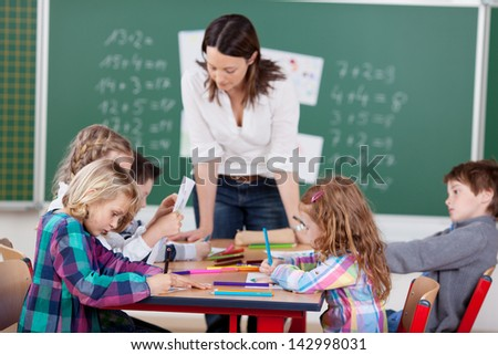 Portrait of teacher helping her busy students in art class - stock photo