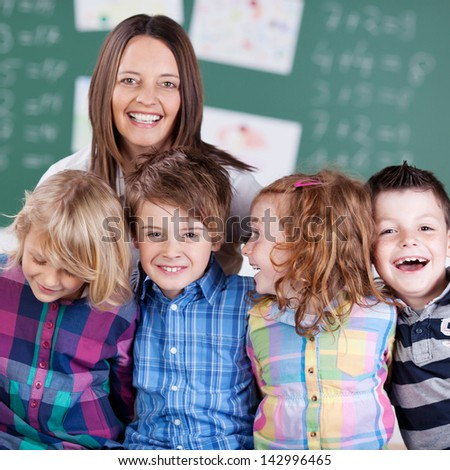 Portrait of teacher in classroom with his laughing students in the classroom - stock photo
