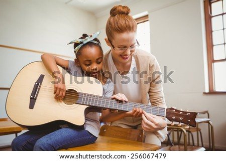Portrait of teacher teaching cute little girl to play guitar in classroom - stock photo