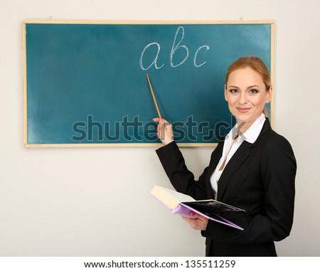 Portrait of teacher woman near chalkboard in classroom - stock photo