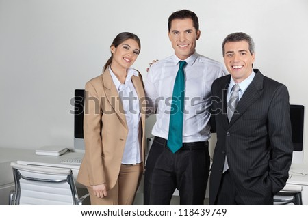 Portrait of team of three smiling businesspeople in the office - stock photo