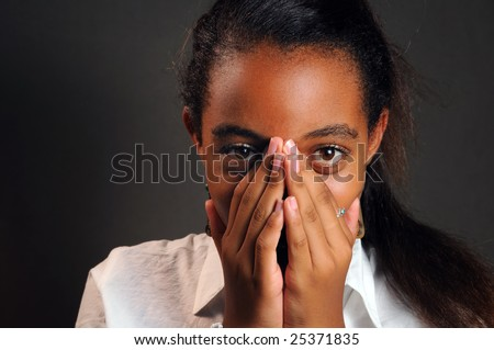 Portrait of teen african girl covering her face - stock photo