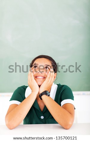 portrait of teen girl daydreaming in classroom - stock photo