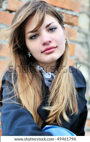 portrait of teen girl near the brick wall - stock photo